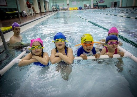 Four kids taking swim lessons
