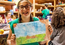 Kingswood camper holding up painting in arts & crafts