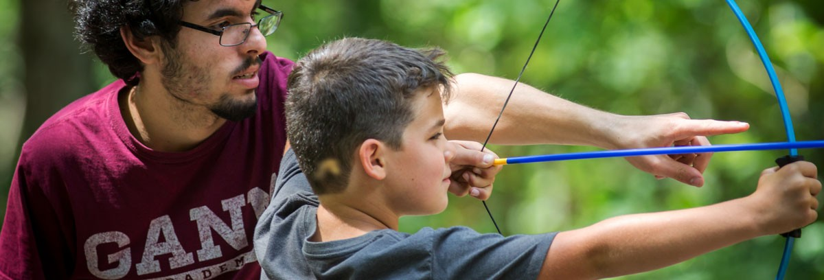teaching a camper to use a bow and arrow