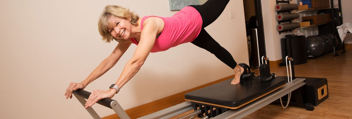 Woman on Pilates reformer in Pilates studio