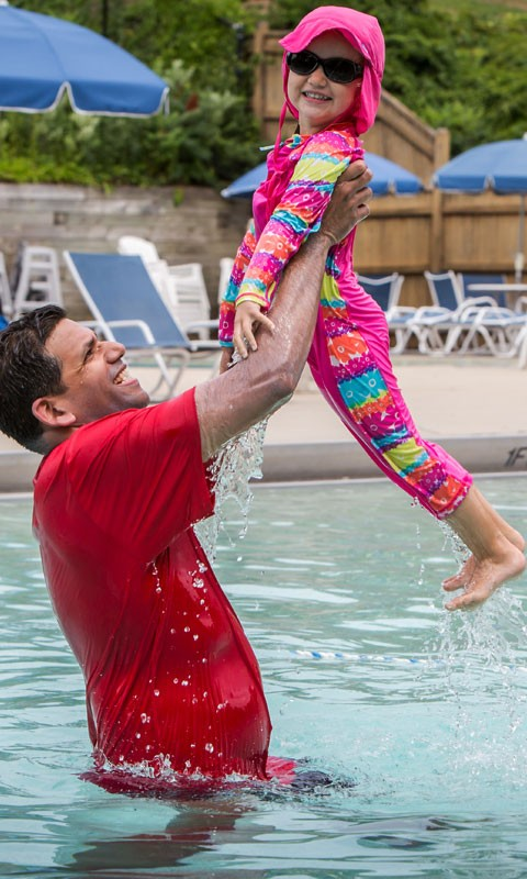 Father throwing daughter in air at JCC Outdoor Pool